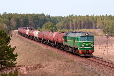 Freight train with fuel passing the woods Stock Photo