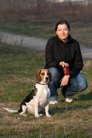 tri: Girl with a tri colored beagle in a park Stock Photo