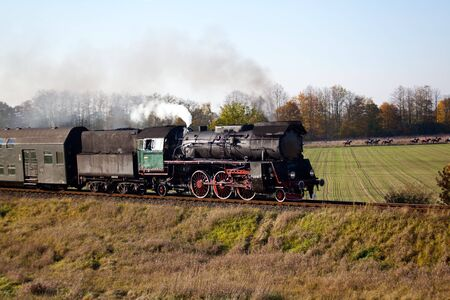 Old retro steam train passing through polish countryside Stock Photo