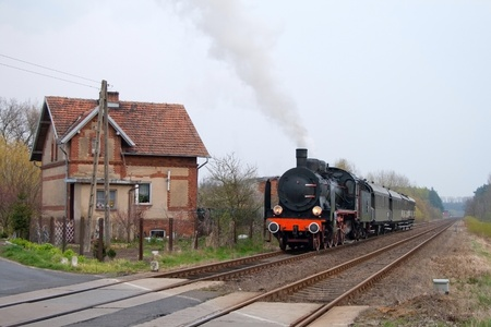 Vintage steam train passing through countryside photo
