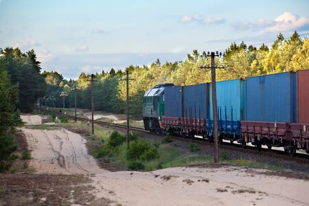 intermodal: Freight train hauled by the diesel locomotive passing the forest