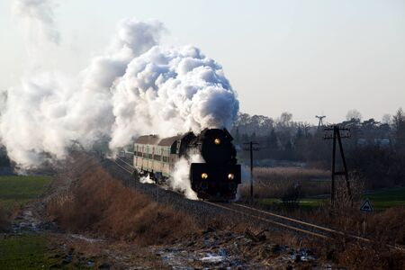 Vintage steam train passing through countryside, wintertime photo