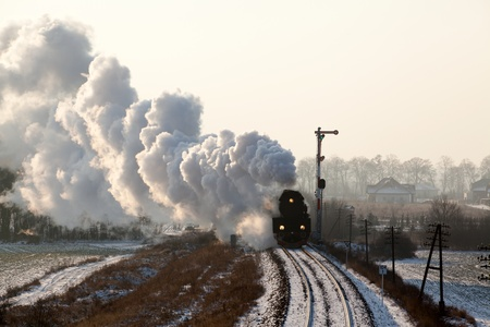 Vintage steam train starting from the station, wintertime photo