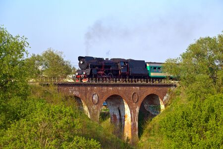Vintage steam passing over the viaduct photo