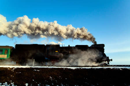 puffing: Vintage steam train puffing through countryside during wintertime