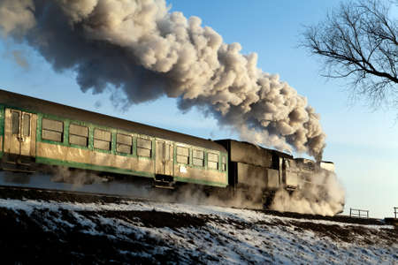 Vintage steam train puffing through countryside during wintertime photo