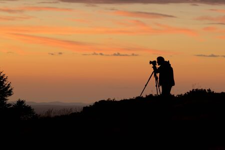 Photographer taking picture of sunset