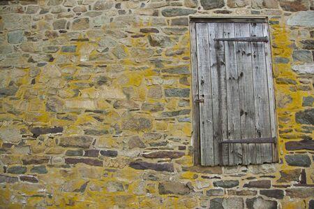 Stone wall with old barn door Stock Photo
