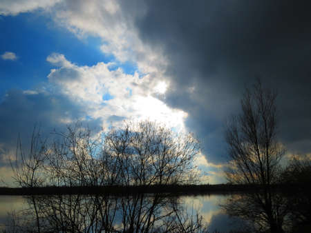 Sun breaking through the clouds above a lake photo