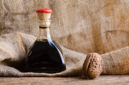 bottle of balsamic vinegar with walnut Фото со стока