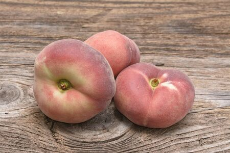 flat ripe peach on a wooden background