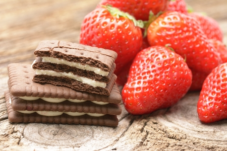 Cocoa biscuits and strawberries isolated on wooden background Stock Photo