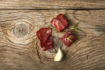 Italian prosciutto crudo or jamon with rosemary and garlic on wooden table