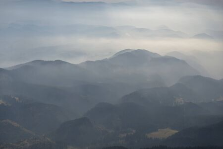 Foggy layered mountain landscape in Piatra Craiului mountains