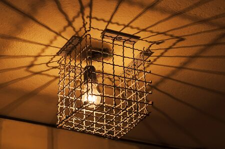 are trapped: Caged light. Light bulb trapped in a cage. Anti-theft protection Stock Photo