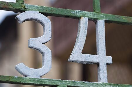 34: Number 34 on gate. Decoration on a fence. Exterior