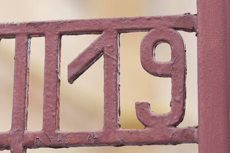 19: Number 19 on gate. Decoration on a fence. Exterior