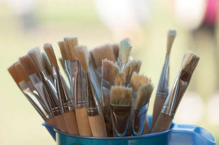 recipient: Painting brushes in a plastic recipient near a window