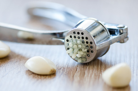 kitchen appliances: Grarlic press and peeled garlic cloves on a wooden table