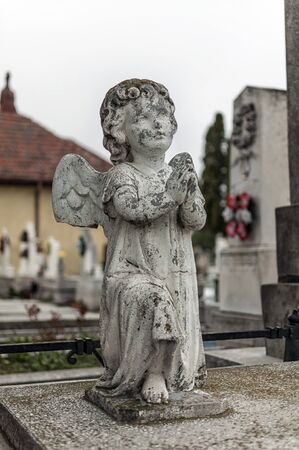 Angel watching over a tombstone. Cemetery figurine. Aged marble Stock Photo