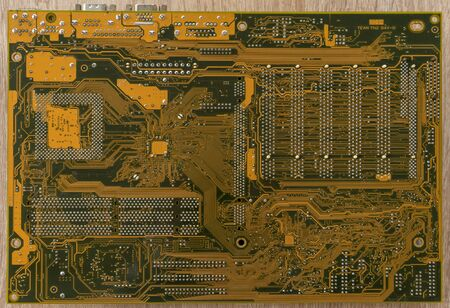 Close-up of an PC motherboard on a wooden table. Circuit path. Bottom view.