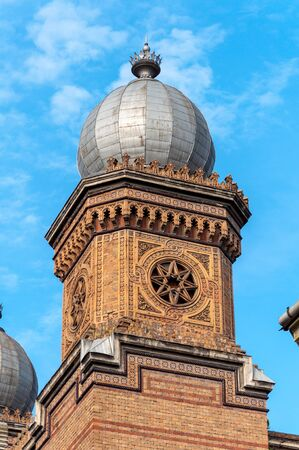 Tower of an old synagogue with a small onion dome. Building made of bricks. Banque d'images - 129569542