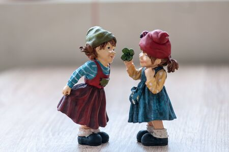 Close-up of two garden gnomes on a wooden table. Gnomes talking
