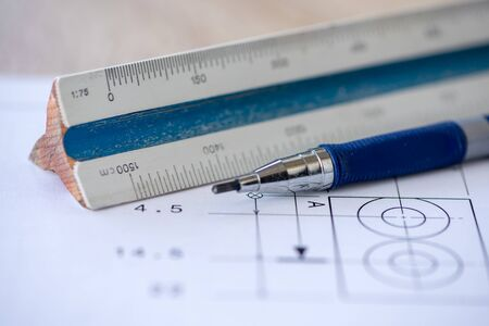Close-up of a wooden ruler and a pencil with a blueprint in the background. Architect tools. Selective focus.