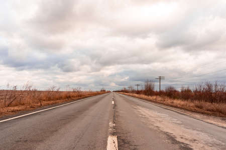 View of an empty road outside the city. Telegraph poles. Clouds in the sky.