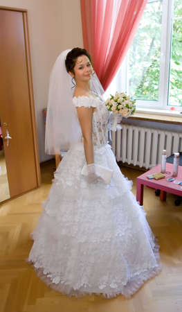 beautiful young bride with wedding bouquet of roses photo