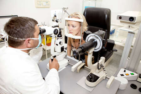 medical attendance: Doctor,examining a patient in ophthalmology laboratory Stock Photo