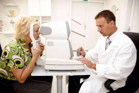 examenes de laboratorio: Doctor, examinar a un paciente en la clínica de oftalmología Foto de archivo