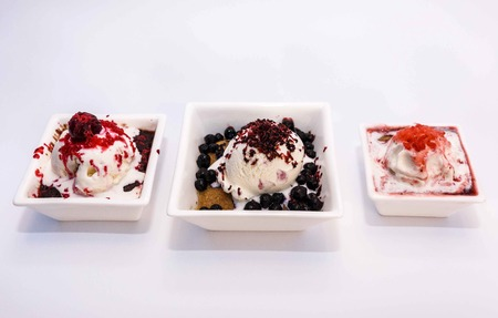 Ice cream with berry stuffing, cream, strawberries, blueberries and cookies with chocolate
