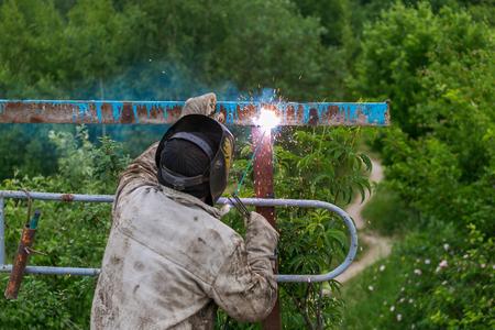 blowtorch: Welder at work. Welder cooks metal grate on the ground blowtorch on the ground in special clothes and mask welder. Stock Photo