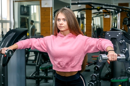 Beautiful girl is engaged in a gym