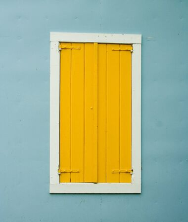 Yellow Shutters on Window on Blue Stucco Wall