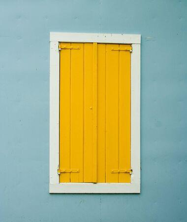 stucco wall: Yellow Shutters on Window on Blue Stucco Wall