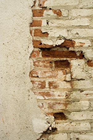 Gros plan de la détérioration de stuc et de mur de briques