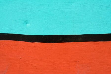Closeup abstract of orane and turquoise with black stripe stucco