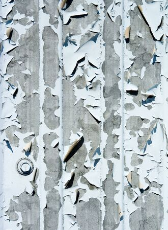 Closeup abstract of peeling blue paint on metal door