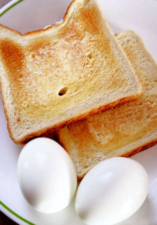 Two hard boiled eggs with buttered toast photo