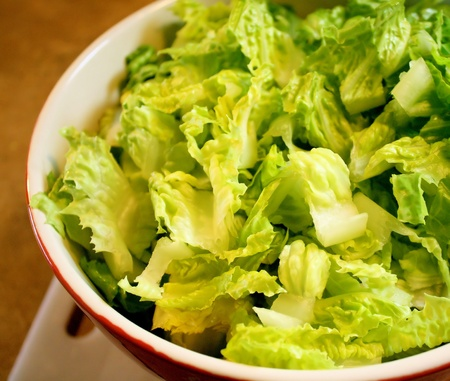 romaine: Fresh Romaine Lettuce In Serving Bowl - on cutting board