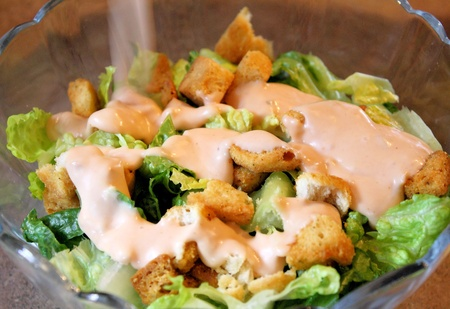 Garden salad with salad dressing being poured and croutons