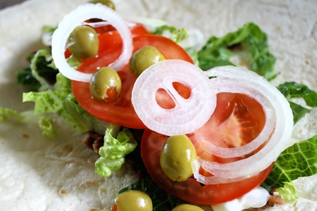 Tortilla with fresh toppings - olives, tomatoes, onions, lettuce and refried beans  Stock Photo - 9779535