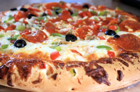 Pizza with pepperoni, sausage and veggies photo