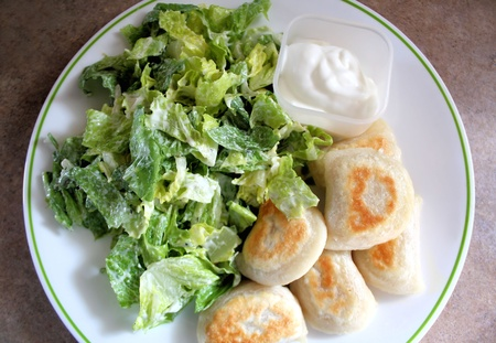 caesar salad: Perogies with Caesar salad & sour cream Stock Photo