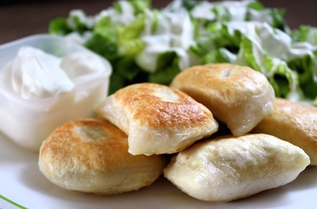 Perogies, sour cream and side salad Stock Photo