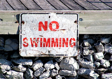 no swimming: An old and worn No Swimming sign posted on boating dock Stock Photo