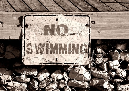no swimming sign: Old and worn No Swimming sign posted on boating dock - (sepia) Stock Photo