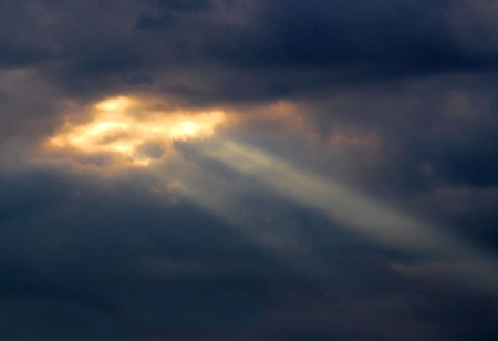 Dark Brooding Clouds With Rays Of Light Peeking Through